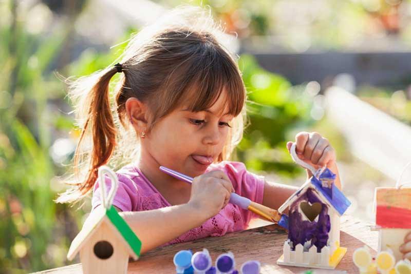 Little Girl Painting A Bird House